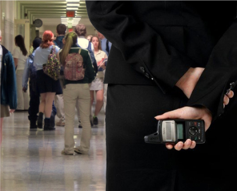 hall monitor holding a two-way radio in a hall full of students